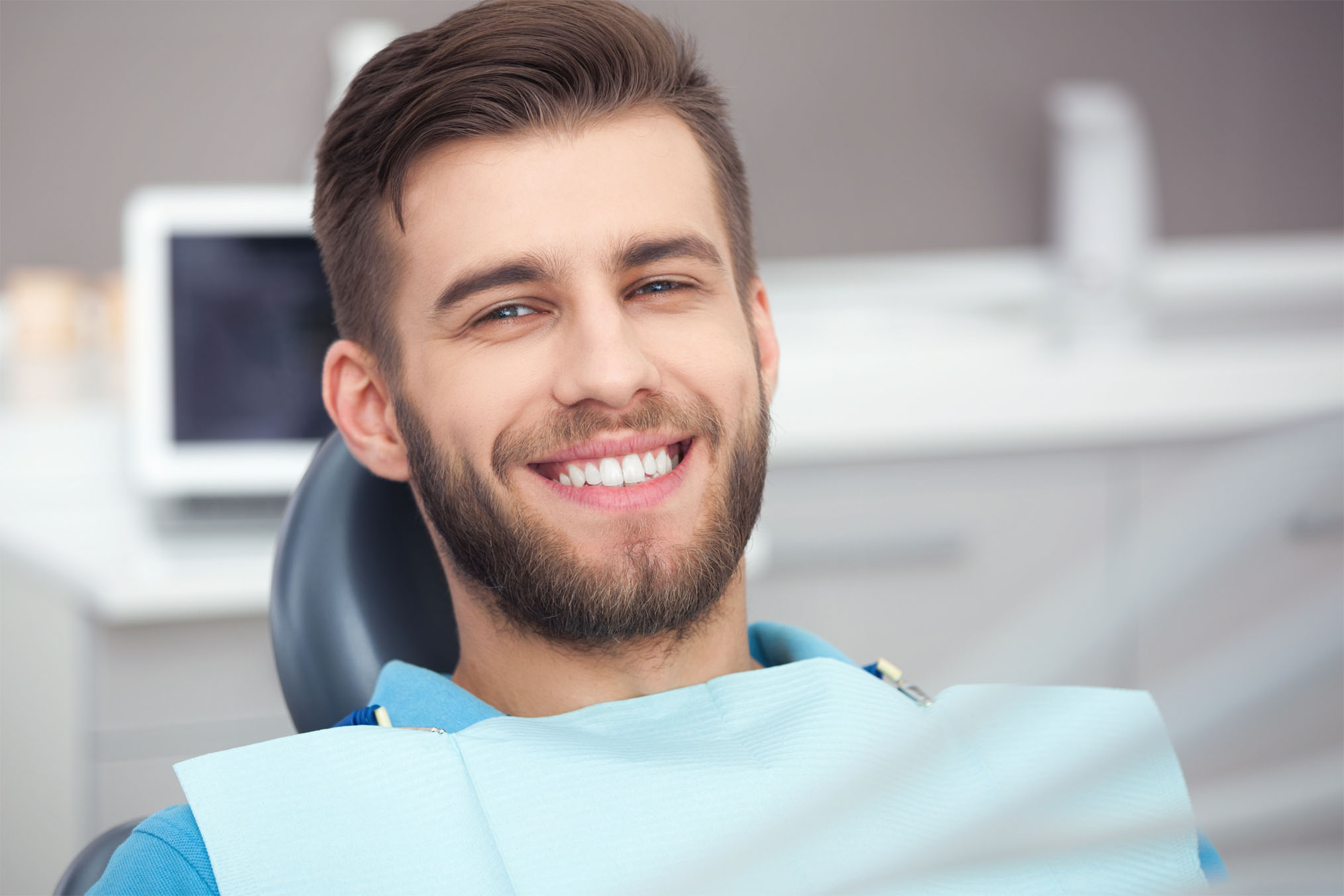 Young male patient smiling in the dental chair