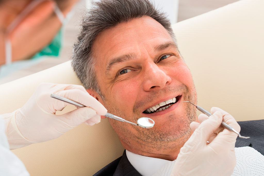 Middle-aged man getting his teeth examined