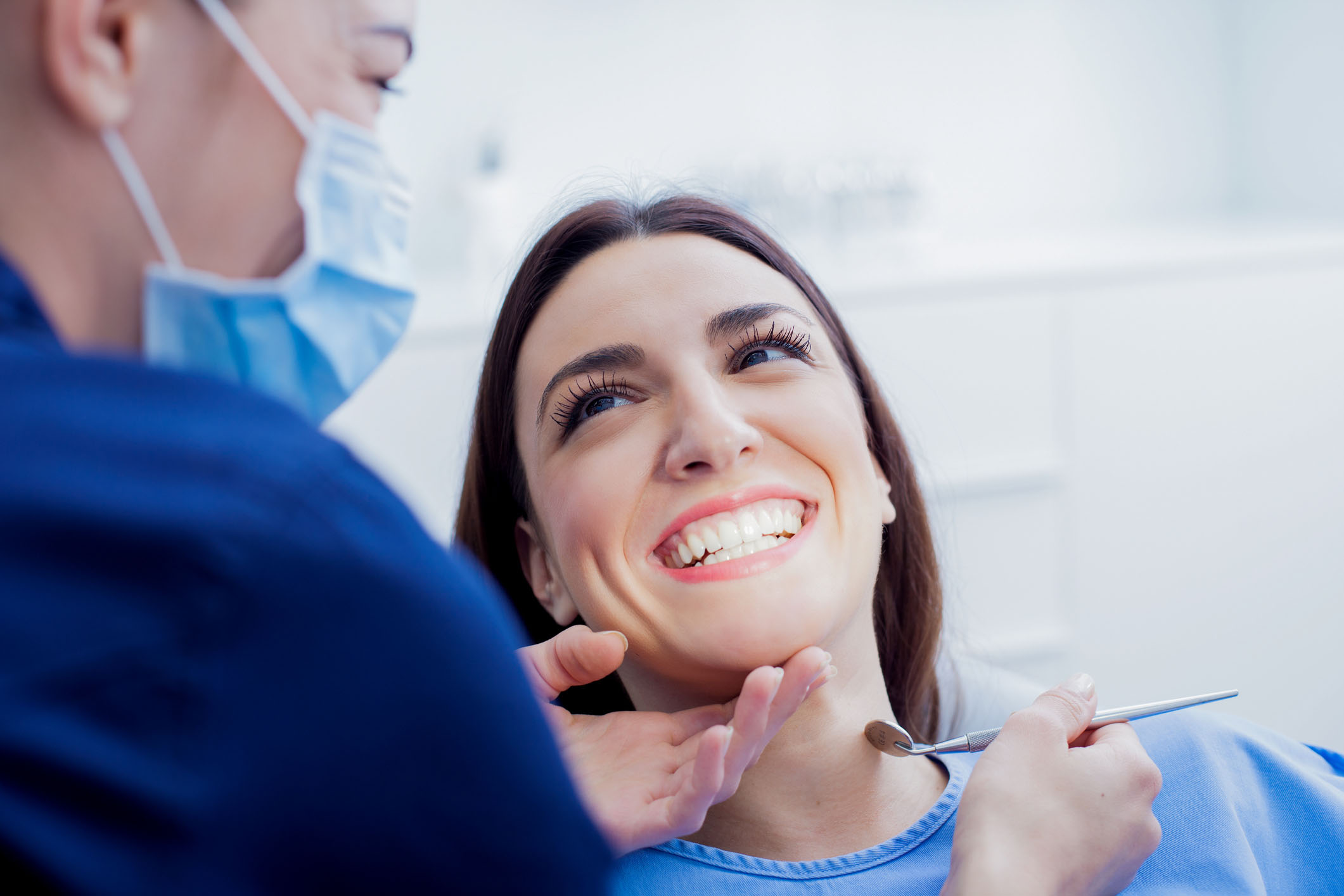 Young female patient smiling as a hygienist cleans her teeth